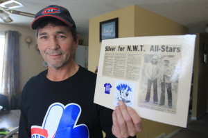 Kevin Daniels holds up a story he saved about bringing home a silver medal as part of the 1979 fastball team that made it to the Canadian Championship finals. He's on the right in the photo with the story.