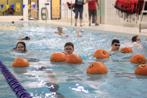 Reegan Junkind, left, Caleb Brockway, centre, and Mason Walters search for a pumpkin with their name on it during a Lions Swim Club practice at the Hay River Aquatic Centre on Oct. 30.