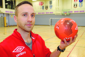 Mark Miehm, a volunteer coach, holds the smaller and heavier soccer ball used for futsal.