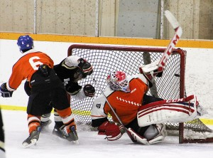 Paul Bickford/NNSL photo Hay River Huskies defenseman Brian Steven, centre, focuses on the rushing Kyle Hallett of the Yellowknife Flyers in action on Saturday night, while goalie Kris Rewega stands ready to defend his net.