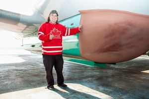 Evan Kiyoshi French/NNSL photo Mikey McBryan, of Buffalo Airways, stands with the recently-retrofitted Lockheed Electra transport plane the company has spent $4 million turning into a water bomber for use against NWT wild fires.