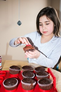 Diana Yeager/NNSL photo Daide Colemen, 8, prepares muffins ahead of a Feb. 14 bake sale to raise money for the Soup Kitchen.