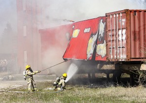 In order to fight a fire inside the building, firefighters take the side off the smokehouse at the Emergency Response Training Centre on Vale Island on May 22.