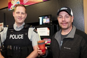 Paul Bickford/NNSL photo John Hill, right, the owner and operator of Super A, holds a Slushie that can be redeemed by any young person receiving a Great Job Ticket from Cpl. Greg Morrow, left, or any other member of the RCMP in Hay River. The RCMP has just launched the initiative to reward good behaviour by young people.