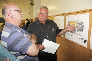 Paul Bickford/NNSL photo Community resident Alvin Pitre, left, listens closely as Dave Brothers, vice-president of Northern operations with Clark Builders, explains plans for a rebuilt Don Stewart Recreation Centre on the site where the existing one now stands.