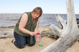 Diana Yeager/NNSL photo April Glaicar collects sand from the shore of Great Slave Lake that she will turn into glass for her jewelry. Glaicar will be travelling to Inuvik this week for the Great Northern Arts Festival where she will display her craft.