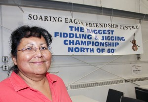 Paul Bickford/NNSL photo Margaret Jerome, president of Soaring Eagle Friendship Centre, stands next to a banner for The Biggest Fiddling and Jigging Championship North of 60 in September. The Friendship Centre and the Hay River Metis Government Council has entered into a partnership to present the event.
