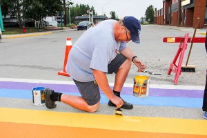 Paul Bickford/NNSL photo Mayor Brad Mapes helps paint the crosswalk in front of NWT Centennial Library in the colours of the LGBTQ rainbow flag on Aug. 5.