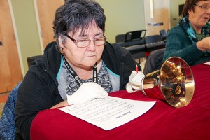 Pat Burnstad looks over a sheet of music, while a handbell is put to the side for a moment.