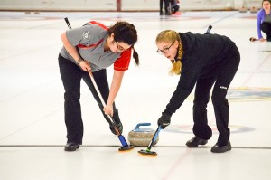 James McCarthy/NNSL photo Katherine Lenoir, left, and Nicole Griffiths – members of the Zoey Walsh curling team from Hay River – sweep a rock during the NWT junior championships earlier this month in Yellowknife.