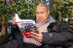 Chief Roy Fabian of K'atlodeeche First Nation reads one of the many novels by Stephen King.