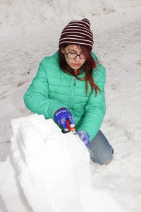 NNSL file photo Kleo Skavinski sculpts snow in front of NWT Centennial Library during the first Winter Celebration on Feb. 6, 2016.