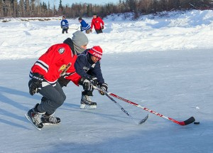 NNSL file photo Freddie Walls, left, and Finno Celestin battle for the puck in early March of last year during the annual Polar Pond Hockey tournament on the Hay River.