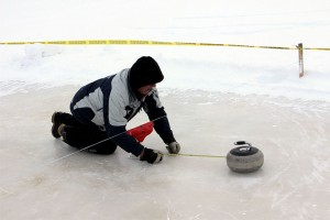 Paul Delorey measures the distance of a rock from the target – a small banner above the ice substituting for curling rings.