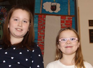 Paul Bickford/NNSL photo Nora Lecouter, left, and Payton Walters, two Grade 5 students at Princess Alexandra School, stand in front of a three-metre-high drawing of a well that will keep track of donations to help build a real well in Africa.
