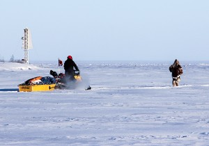 Paul Bickford/NNSL photo Followed by a Canadian Ranger on a snowmobile, Brad (Caribou Legs) Firth runs out of the Hay River onto Great Slave Lake on the morning of March 4.