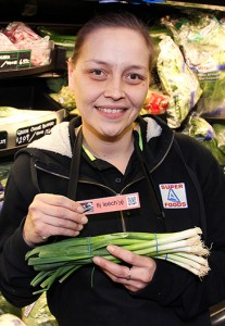 Paul Bickford/NNSL photo Pam Balsillie, an employee of Super A grocery store, displays a tag containing the South Slavey word for green onions. There are about 40 such tags in the store identifying items in the aboriginal language.